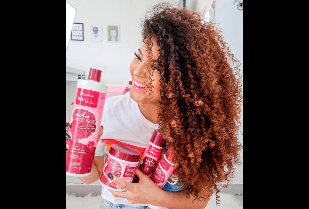 A blogueira cacheada Lari Rezende segura a linha completa Cachos Intensos, do Beleza Natural, com shampoo, condicionador, tratamento e creme de pentear.