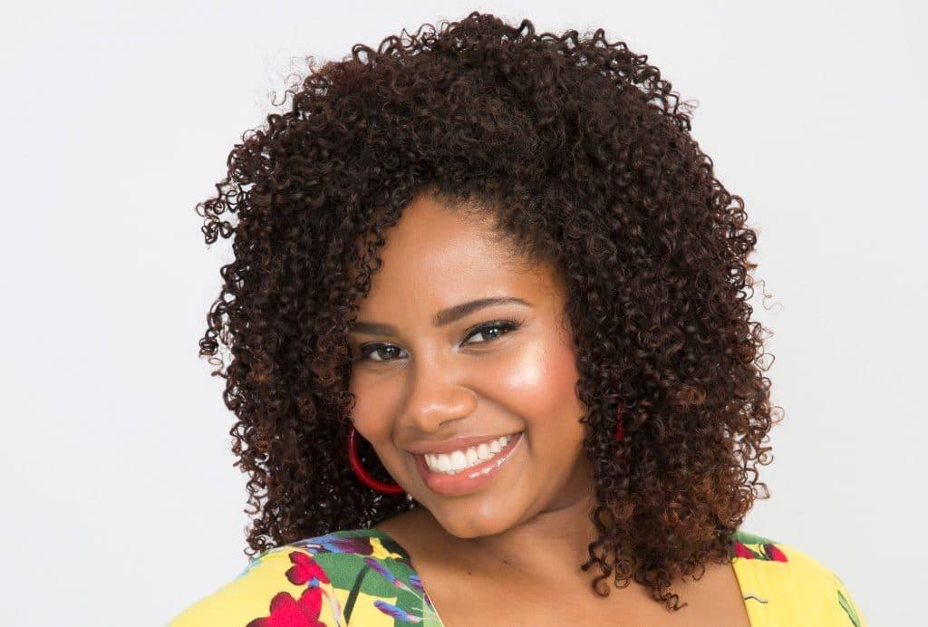 Modelo cacheada  mostra sorrindo seu belo cabelo com relaxamento capilar.