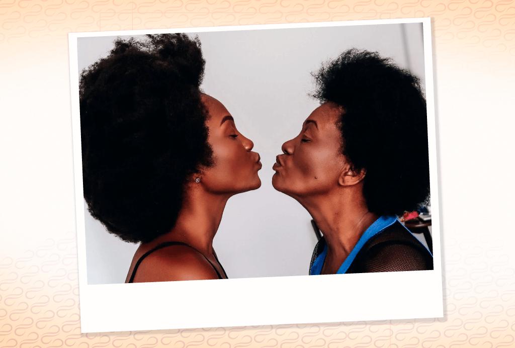 Mulher negra com seu cabelo crespo bem armado está  de perfil fazendo biquinha e fazendo movimento para beijar a mãe que esta a sua frente.