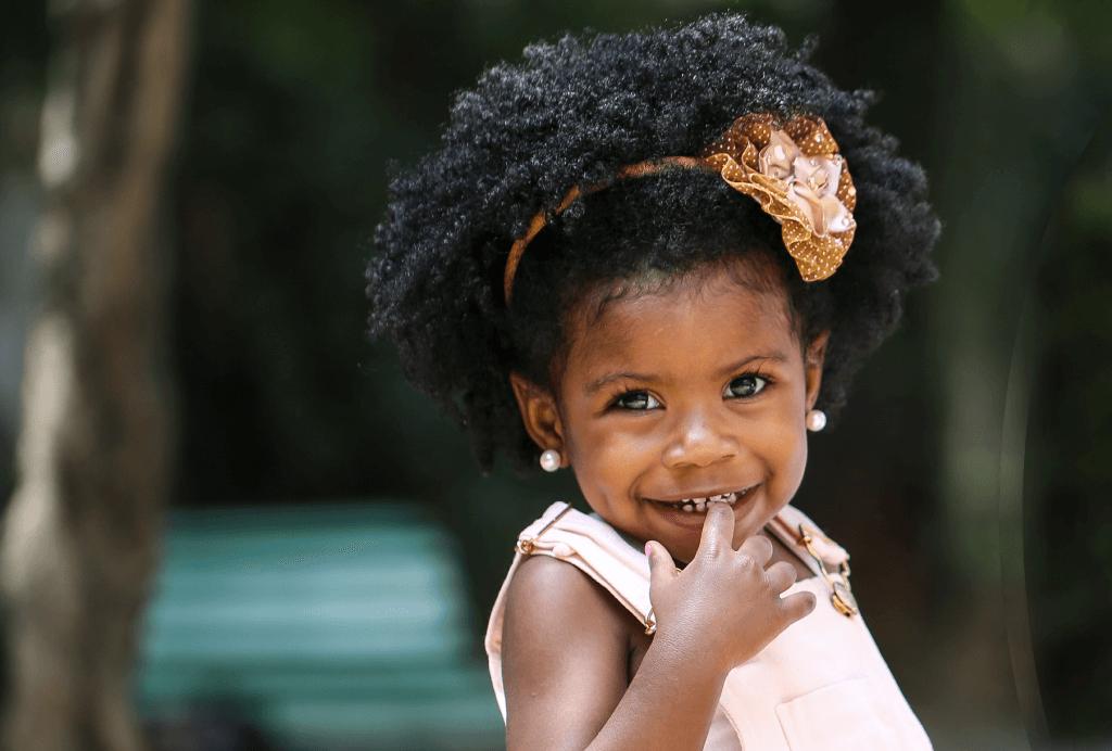 Criança com o cabelo crespo preso com um arco. Ela está sorrindo com o dedo na boca.