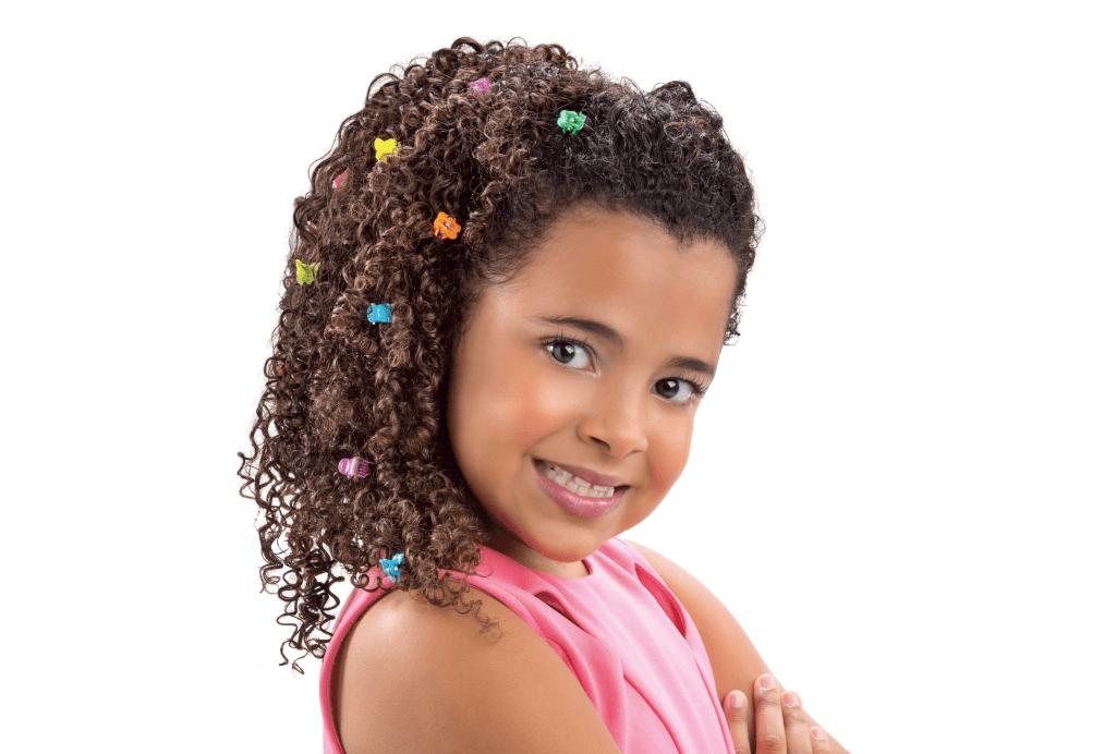 Menina com o cabelo cacheado todo jogado para o lado e alguns prendedores pequenos coloridos.