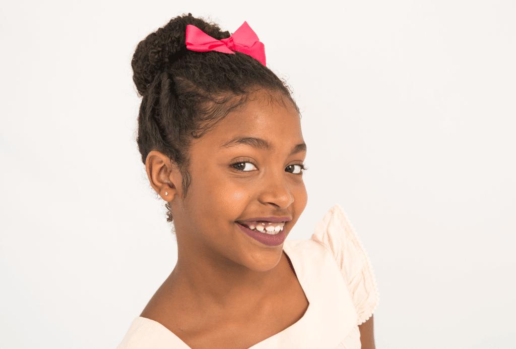 Criança com um coque alto e dois  torcidinhos de cada lado. Penteado está finalizado com um laço rosa. A menina está sorrindo e usa uma blusa branca.