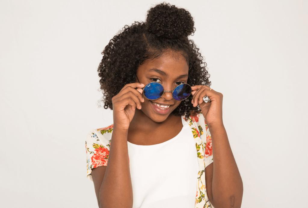 Menina com um coque prendendo apenas a parte de cima do cabelo cacheado. Ela está sorrindo tirando o óculos escuros redondo do rosto.