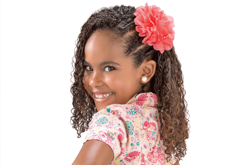 Menina de lado com seu cabelo cacheado preso na lateral com três torcidinhos e uma flor prendendo.