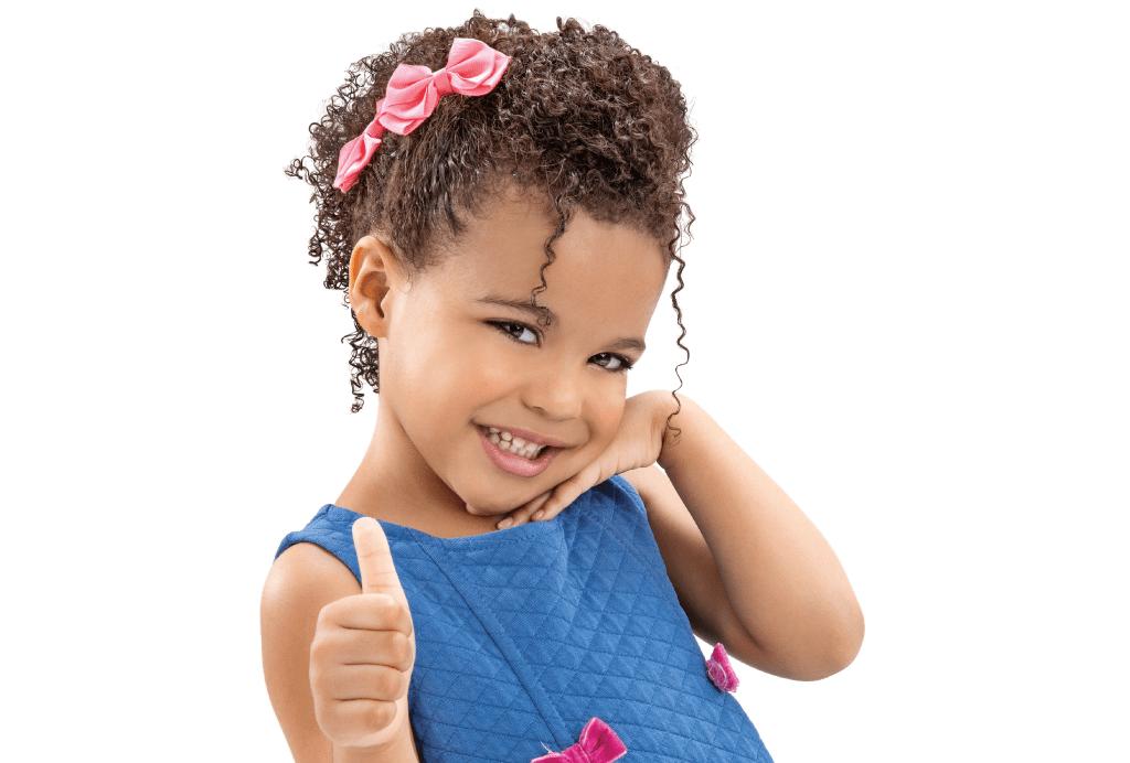 Criança fazendo sinal de positivo com o cabelo preso moicano finalizado com dois laços rosa.