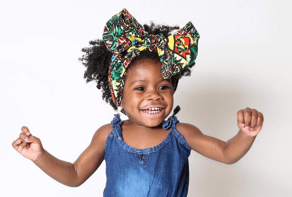 Criança com o cabelo crespo preso total com um faixa multicolorida finalizado com um grande laço. Ela está com os braços abertos, sorrindo e vestindo um macacão jeans.