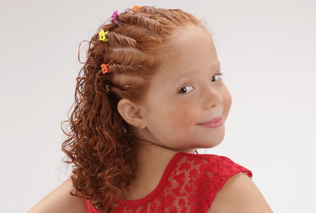 Menina com seu cabelo cacheado ruivo com torcidinhos em toda a cabeça.