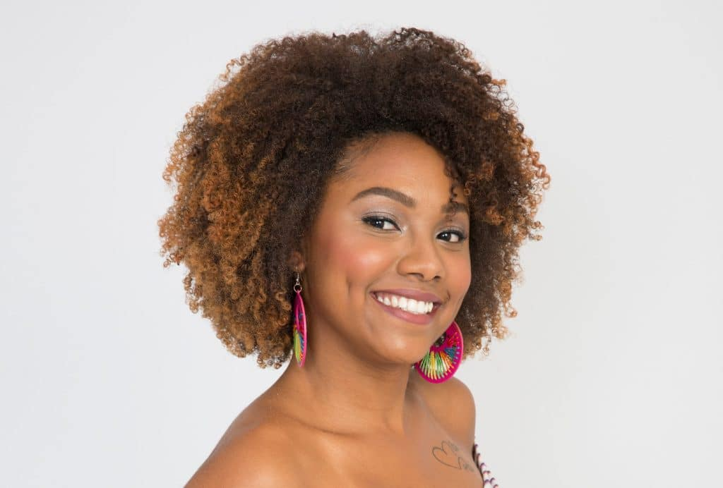Modelo cacheada mostra, com um sorriso, seu cabelo com relaxamento capilar.