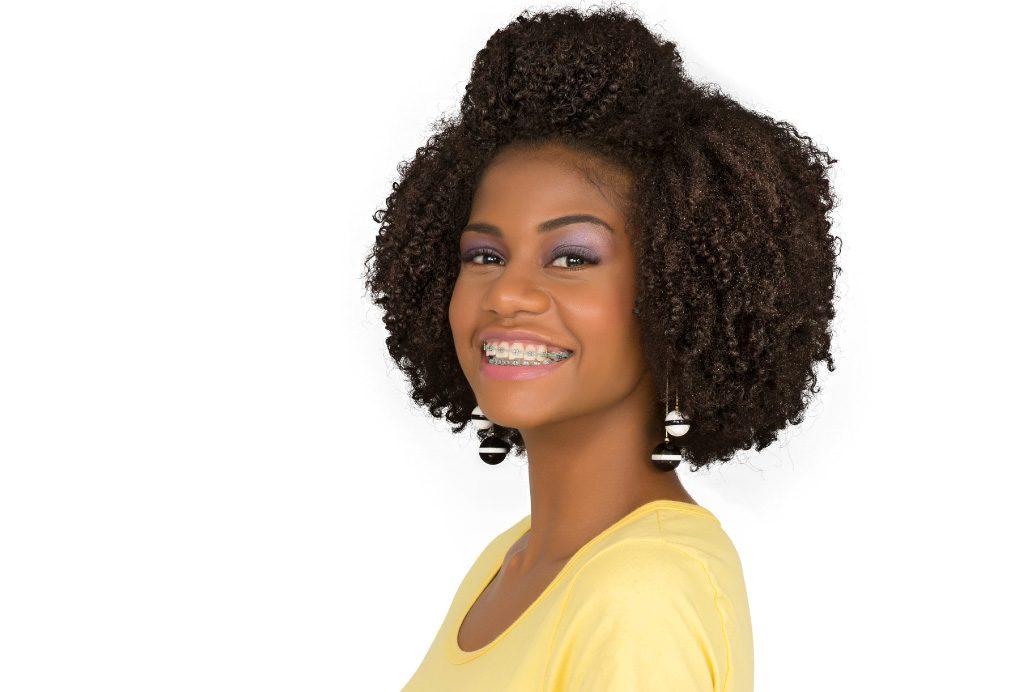 Modelo negra com o cabelo cacheado com o penteado Topete Top Preso.