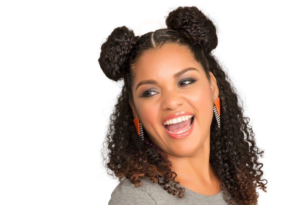 Modelo sorrindo com dois coques apenas no alta da cabeça e o restante do cabelo solto.