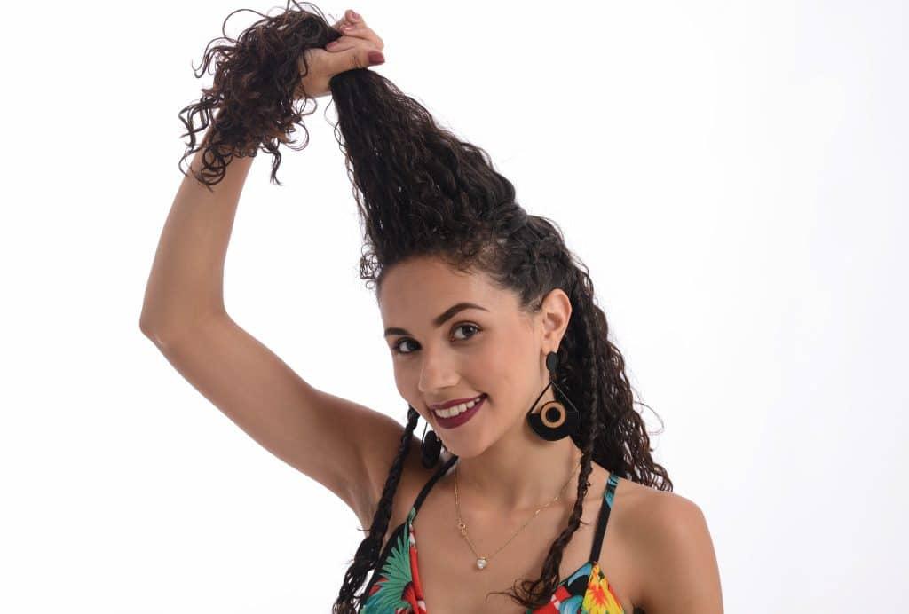 Modelo cacheada segurando a parte de cima do cabelo para cima.