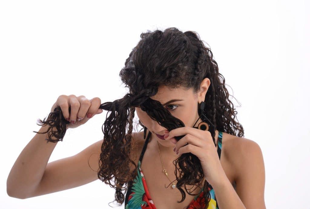 Modelo cacheada segura a mecha de cima do cabelo para a frente e começa a fazer uma trança frouxa.