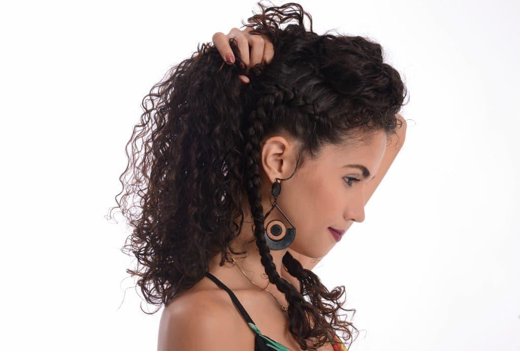 Modelo cacheada segura  parte restante do cabelo em um rabo de cavalo.