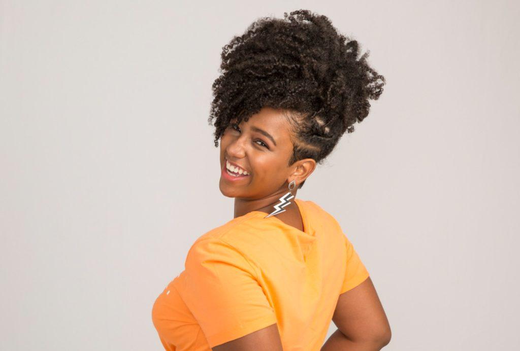 Modelo feminina de perfil sorrindo mostra seu cabelo cacheado com o corte de cabelo undercut, com a parte de baixo dos fios raspada.