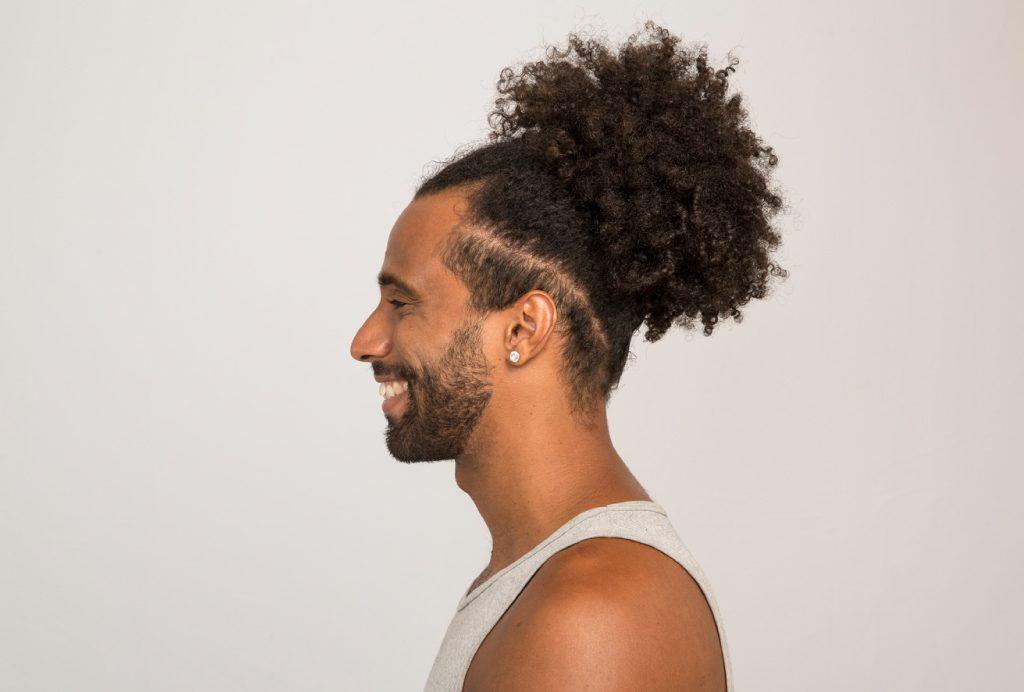 Modelo masculino de perfil sorrindo mostra seu cabelo cacheado com o corte de cabelo undercut, com a parte de baixo dos fios raspada.