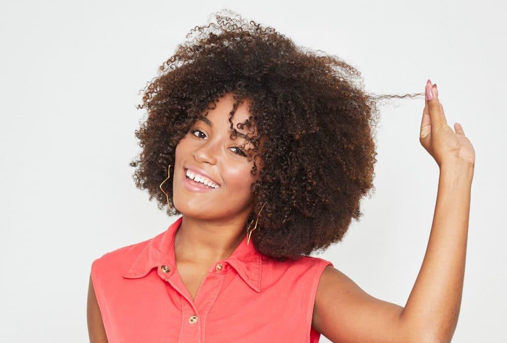 Modelo cacheada com o cabelo super volumoso puxando um cachinho com a mão esquerda e sorrindo para a câmera.