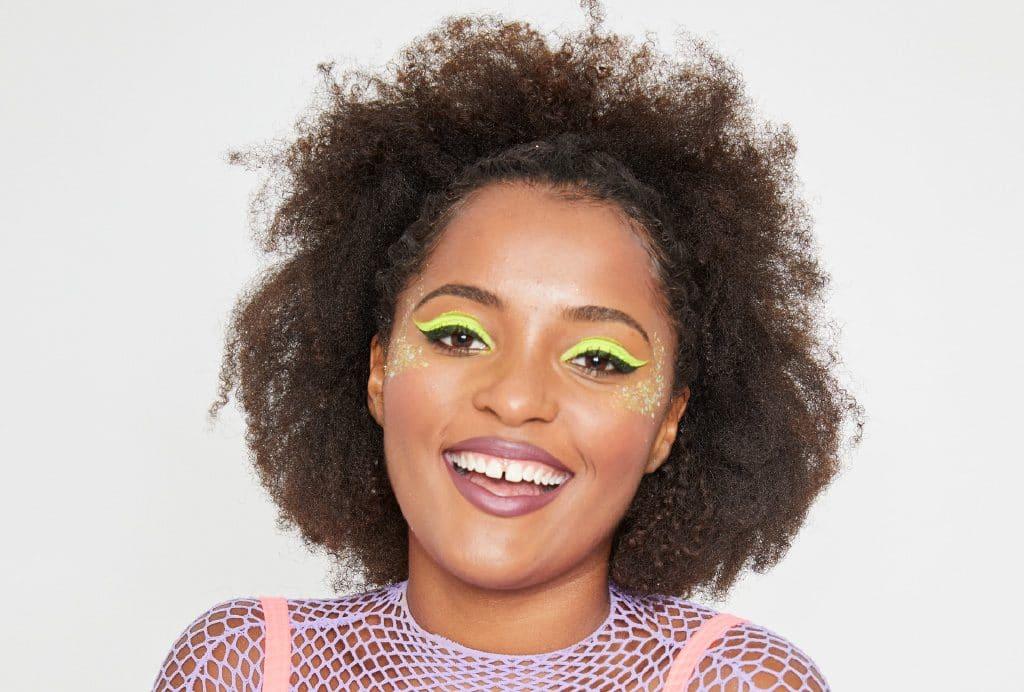Modelo sorri para a câmera com a maquiagem neon pronta.