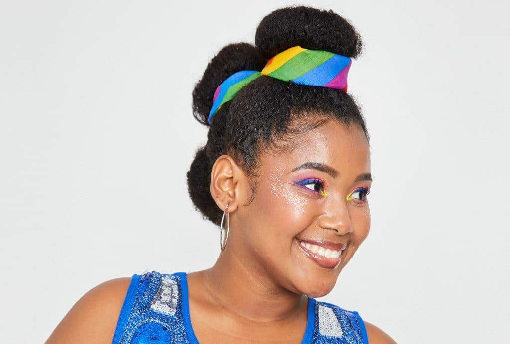 A modelo cacheada está de perfil e mostra o penteado finalizado com um pano colorido, que envolve cada um dos três coques.