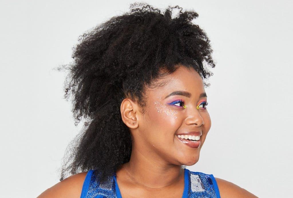 Modelo de perfil mostra o primeiro passo do penteado moicano colorido. Cabelo com uma mecha na parte da frente do cabelo presa  com um prendedor.