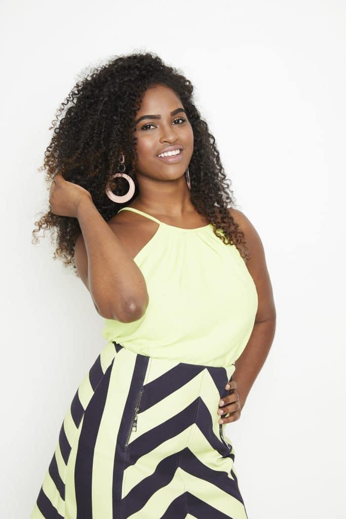 Mulher negra, segurando o cabelo e sorrindo.
