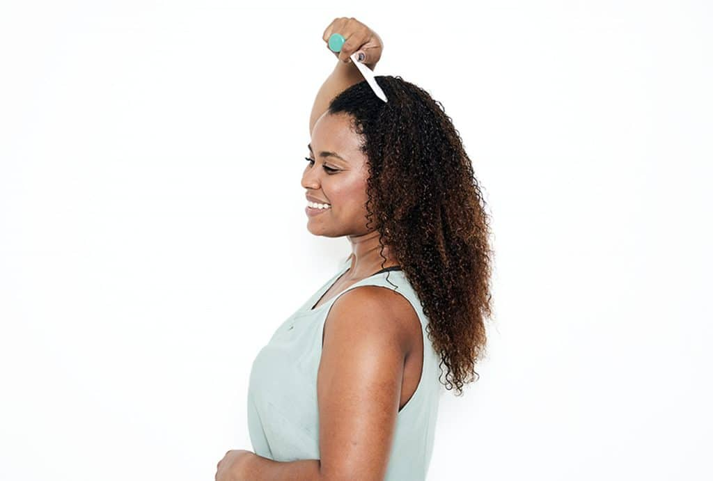 Modelo com o cabelo cacheado passando o pente no topo da cabeça e sorrindo de lado.