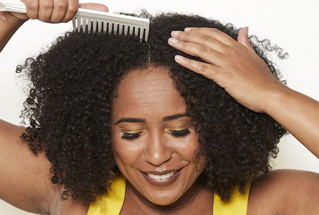 Modelo sorrindo segurando o pente, dividindo ao meio a parte da frente do cabelo.