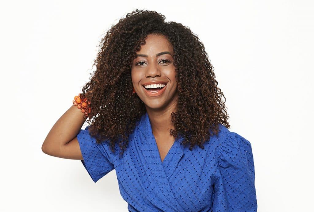 Modelo sorrindo com uma mão nos cabelos na capa da matéria sobre 11 cuidados com cabelos cacheados.