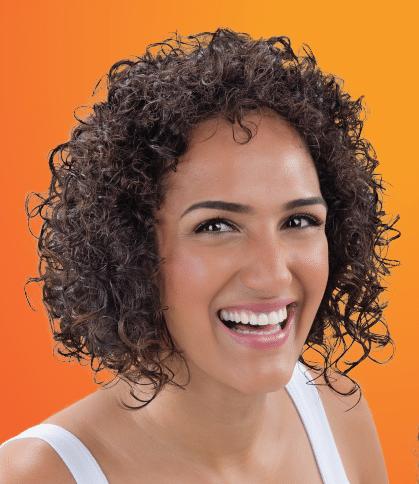 Mulher sorrindo com o corte para cabelo cacheado curto n5 do book de cortes.