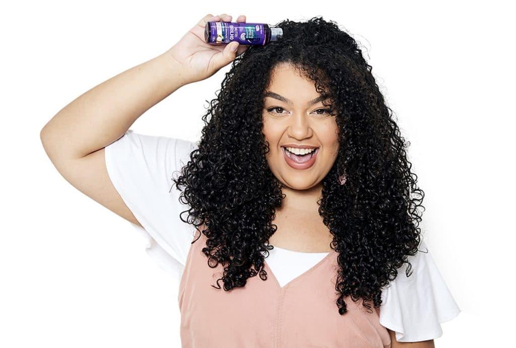 Modelo sorrindo com óleo de umectação na mão, em direção ao cabelo.