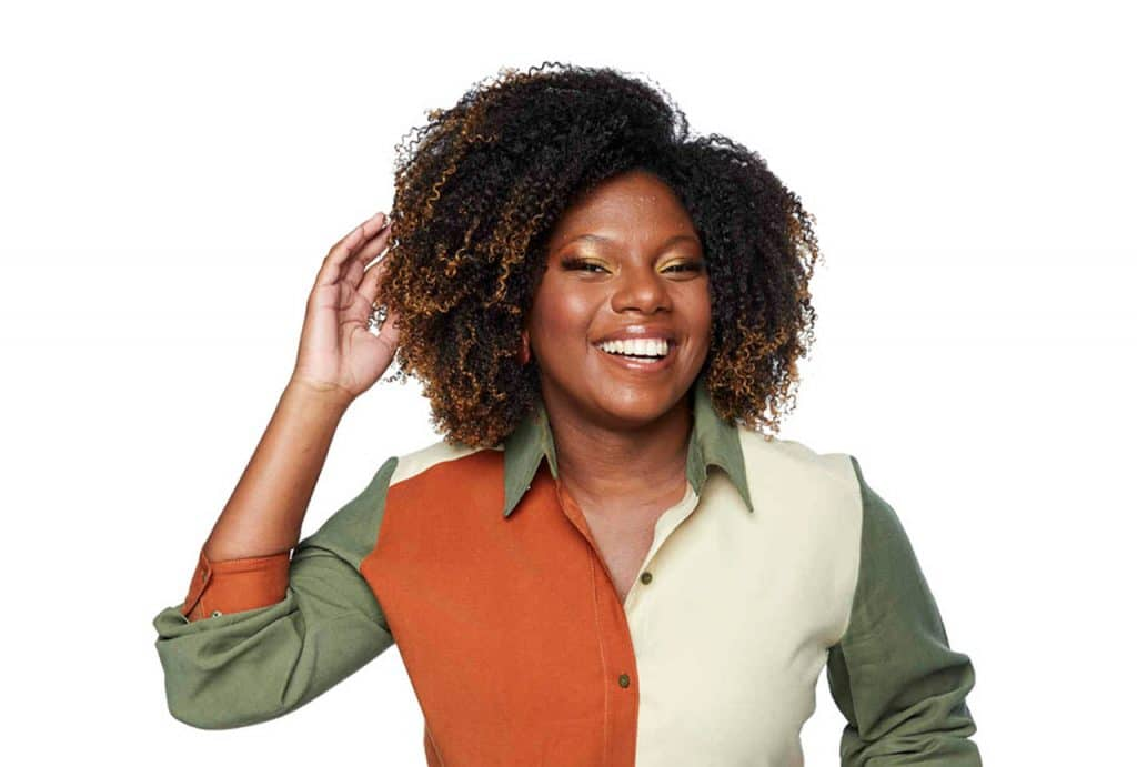Modelo sorrindo para a capa da matéria sobre produtos para cabelo no inverno com a mão direita na cabeça