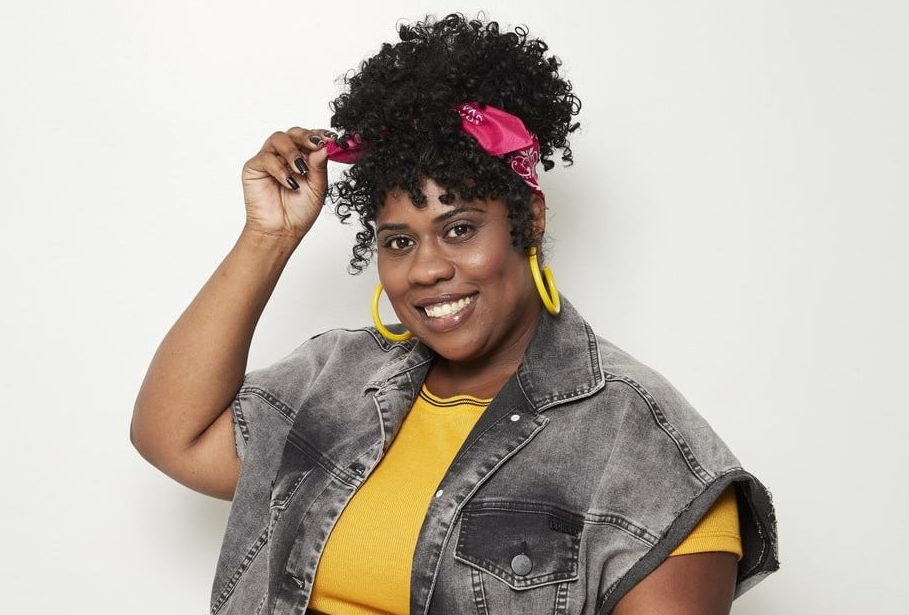 Modelo com penteado de afro puff e bandana, sorrindo segurando a ponta da bandana com a mão.