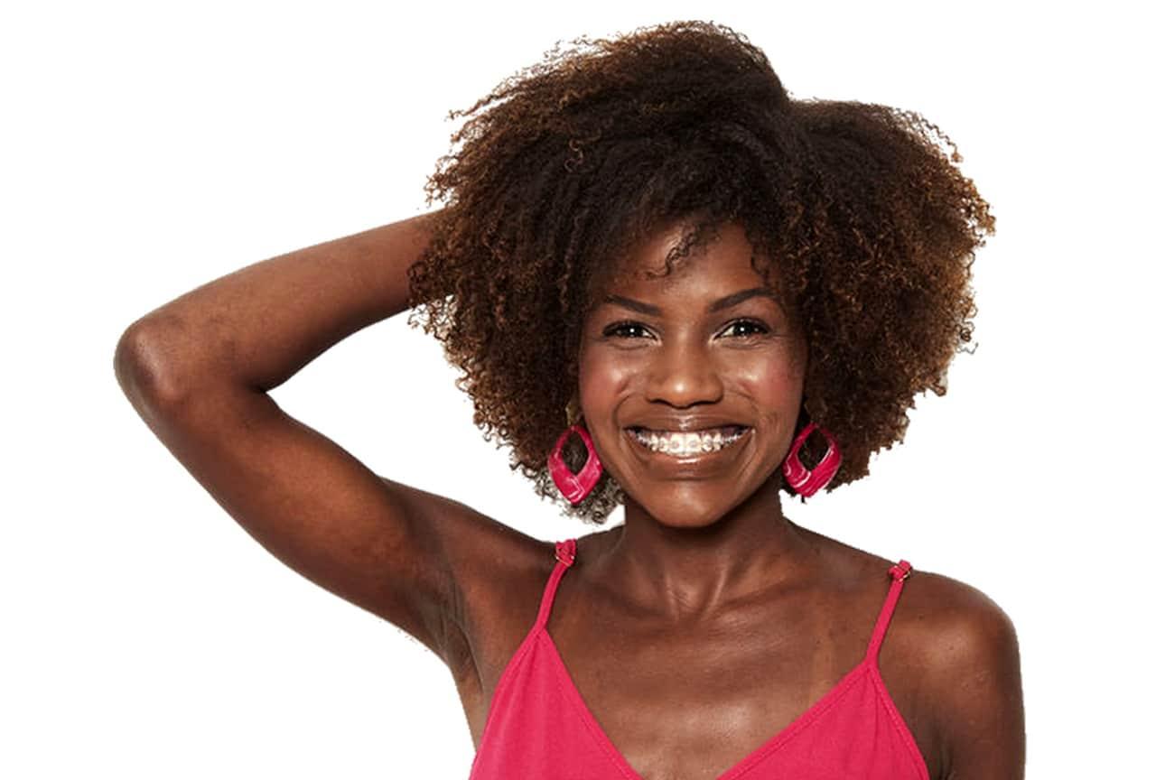 Modelo sorrindo com a mão na cabeça, com os cabelos com relaxante capilar.