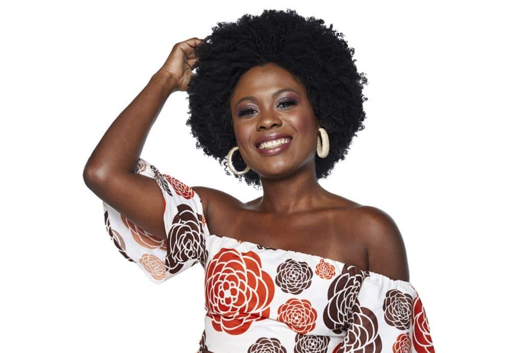 Modelo principal da campanha da linha Óleos Africanos, sorrindo, com a mão no cabelo.