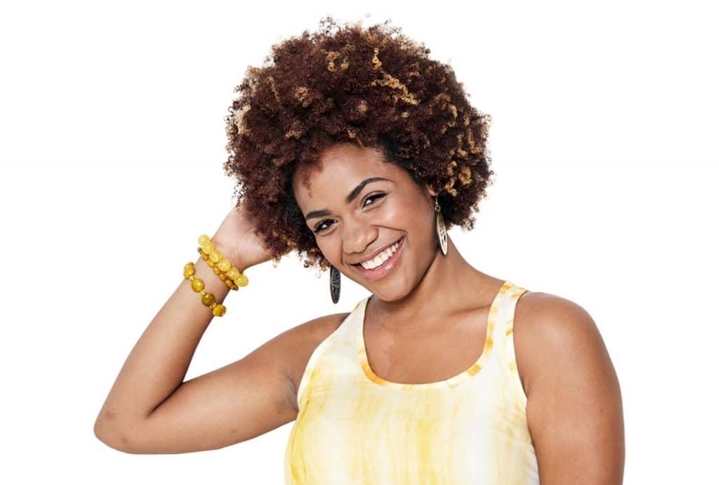 Modelo sorrindo com a mão no cabelo.