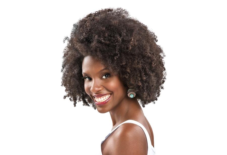 Modelo crespa sorrindo, usando blusa branca e acessórios com detalhes brancos